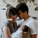 Young family - mother holding baby with father